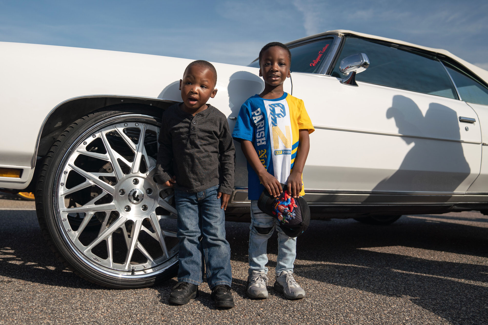 Two kids standing next to big DONK wheels
