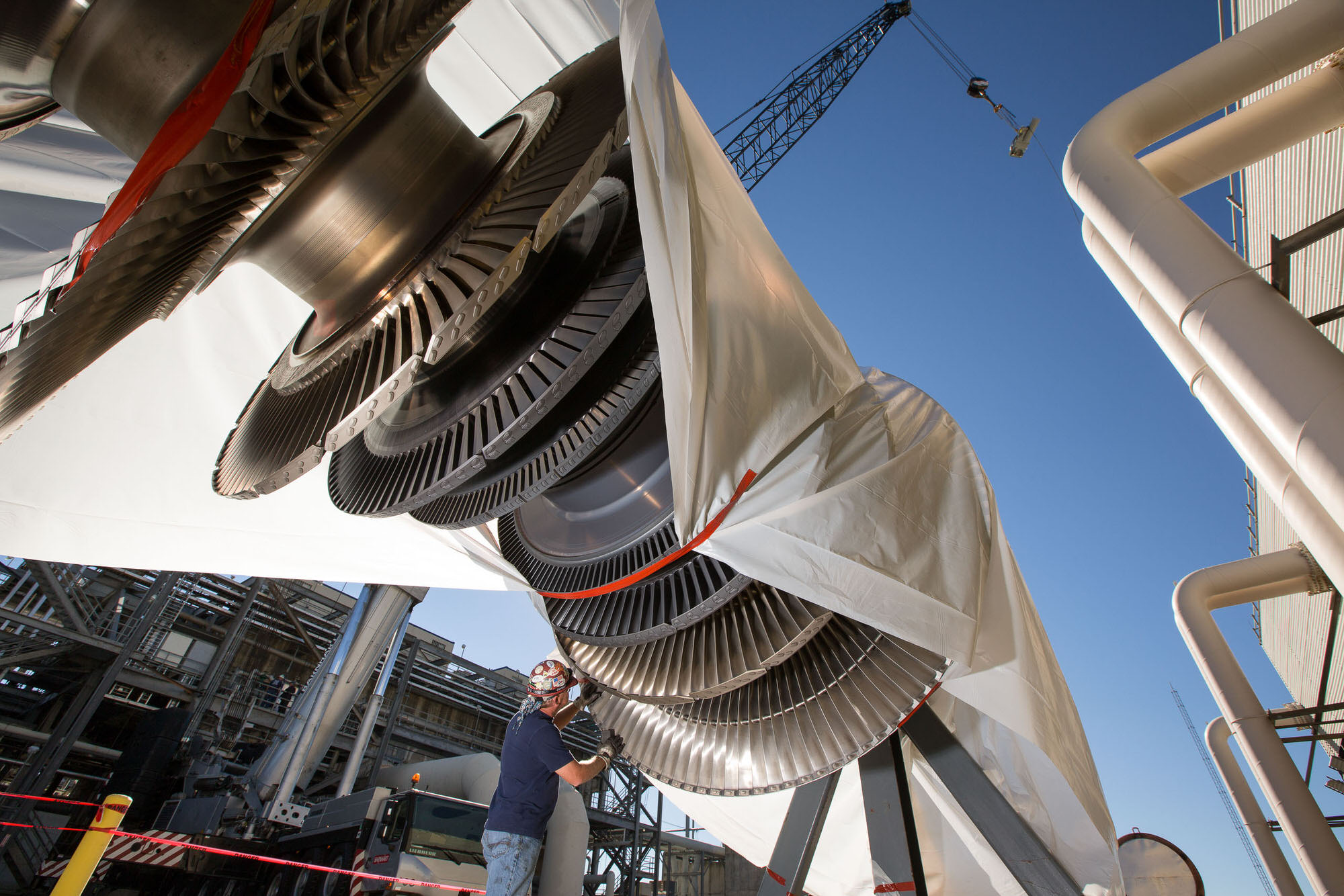 Worker inspecting GE gas turbine for installation at Alabama facility.