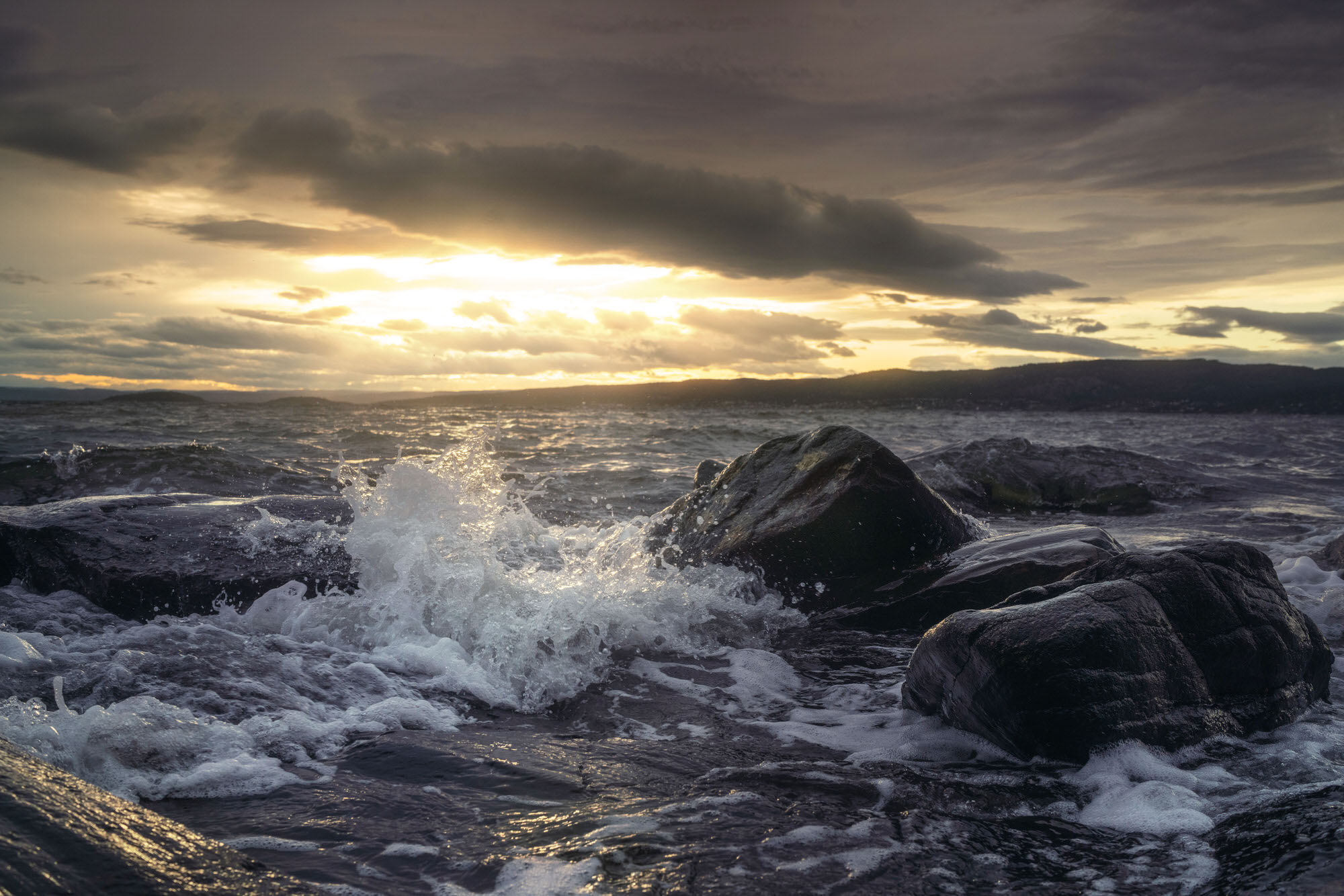 Waves crashing on the rocks of Son, Norway during sunset